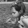 Black and white photo of a girl holding a dandelion and blowing on it