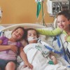three girls leaning next to their sister in her hospital bed and smiling for the camera