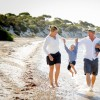 happy family walking together on the beach enjoying summer holidays