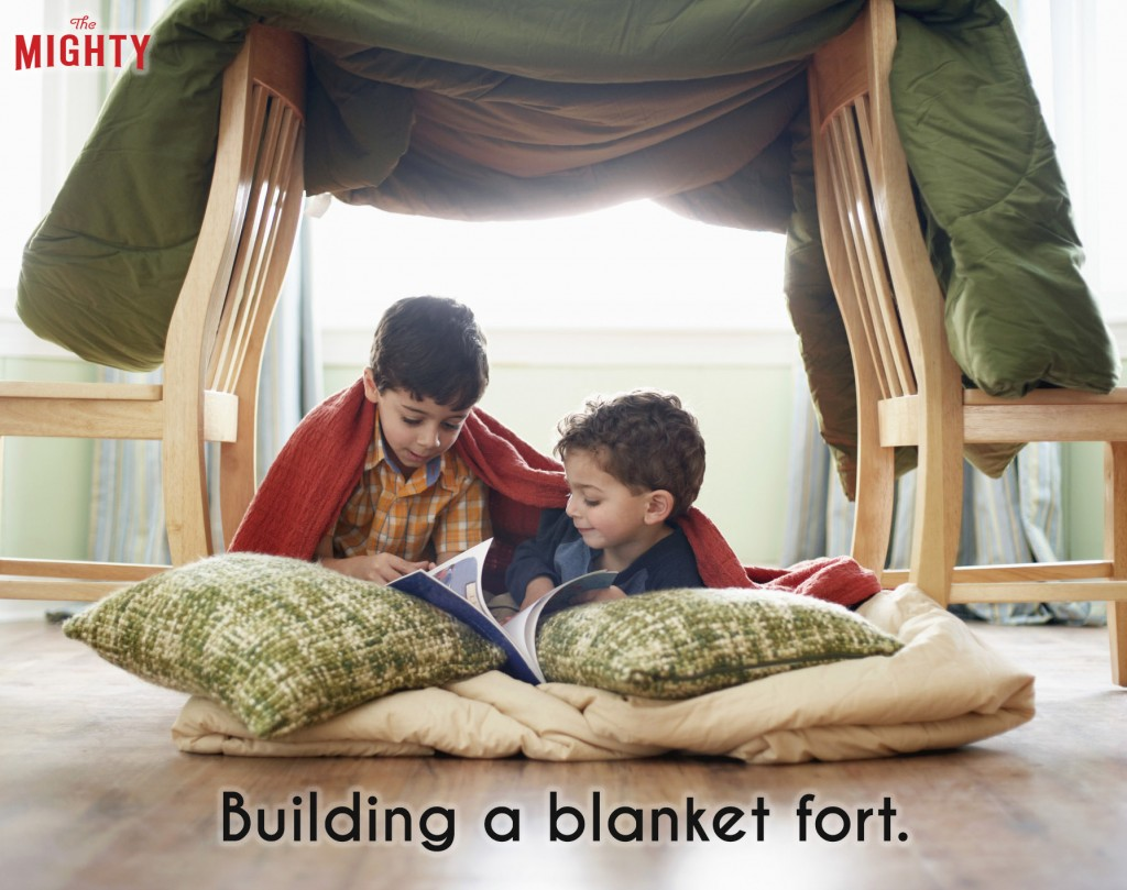 An image of two kids under a blanket fort with pillows. Accompanying text: [Building a blanket fort.]