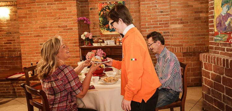 A employee of hotel serves a couple food in a dining room with brick walls.