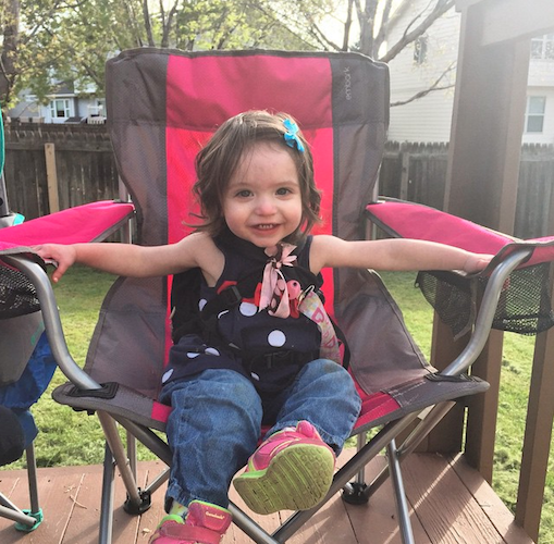 young girl sitting in a chair outside