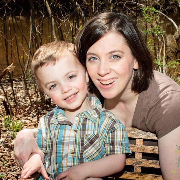 Lori and her son posing near a bench in a park