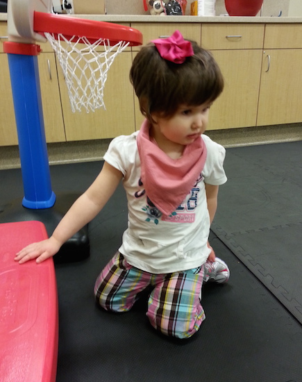 author's daughter sitting next to play basketball hoop