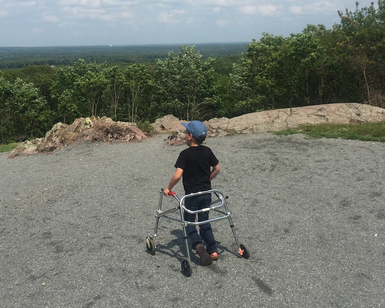 little boy with a walker on a hill