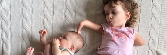 young girl with a limb difference lays next to her baby sister