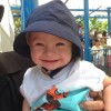 A smiling toddler boy with a hat on his head