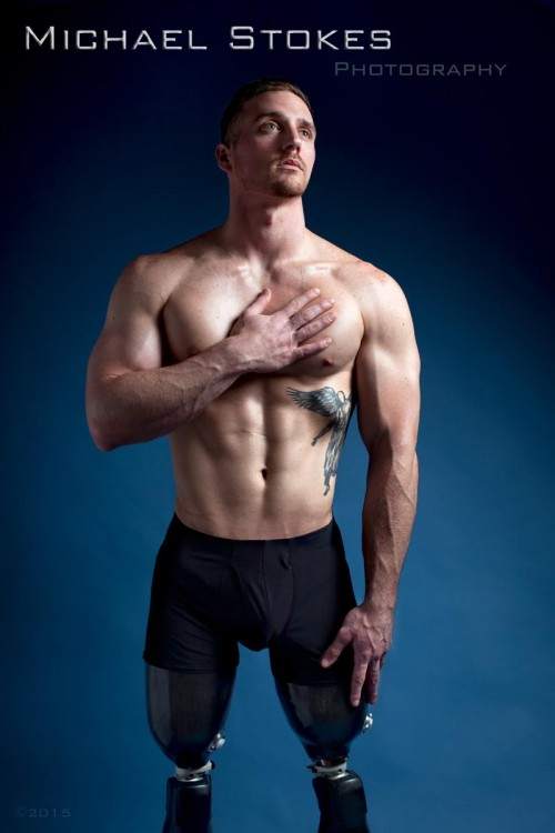 shirtless man with prosthetic legs, posing with hand over his heart