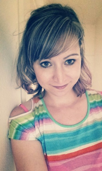 Selfie of a woman with full makeup, and a colorful stripped shirt.
