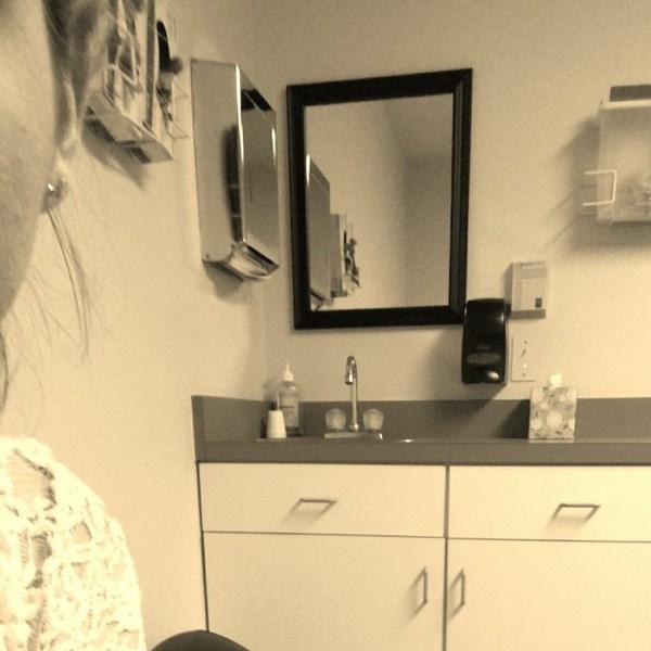 Woman sitting in the bathroom.