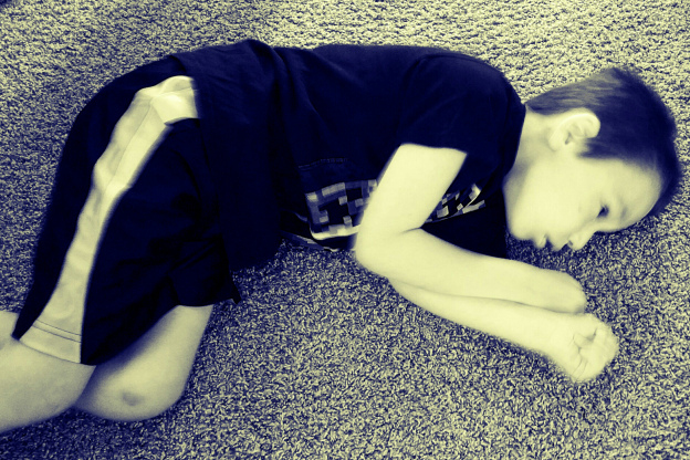 Little boy laying on the floor.