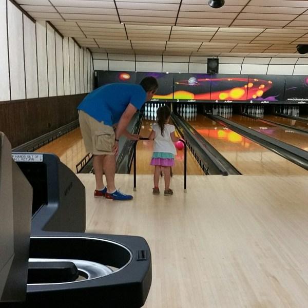 Dad helping his daughter bowl.