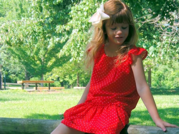 little girl in red dress sitting outside