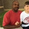 A coach poses with a boy while holding his hand