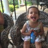 A small girl sits in chair outside smiling