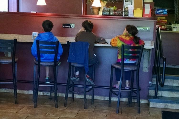 three children sitting in a restaurant