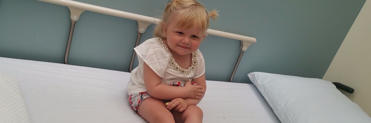 author's daughter sitting on a hospital bed
