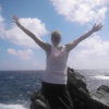 woman extends arms in front of the ocean