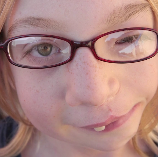 close-up photograph of young girl wearing glasses