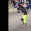young boy dancing and standing on his hands in the street