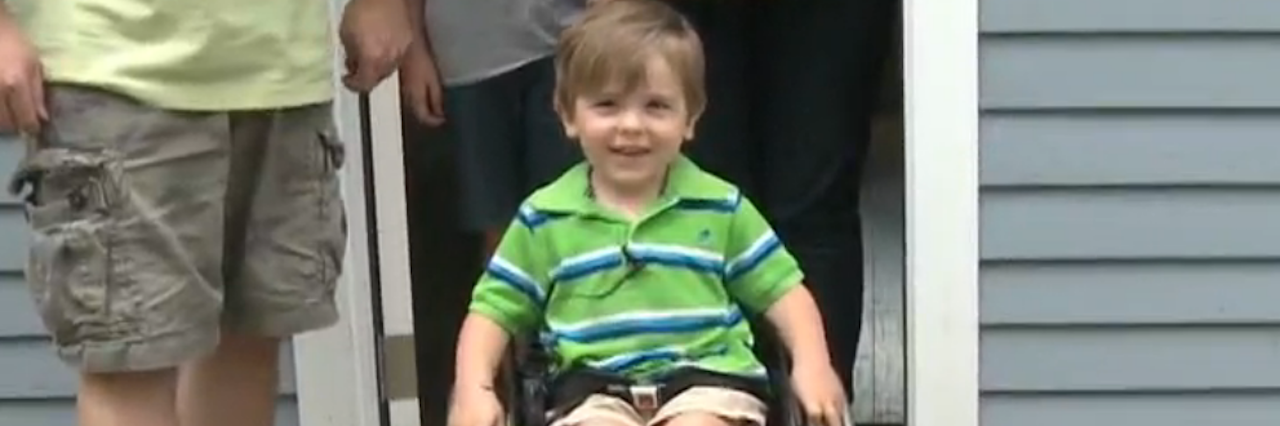 young boy smiling in wheelchair