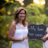 "Two sisters in white dresses outdoors, holding a sign that says, ""Her bun, My oven."""