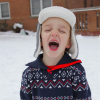 A boy with a hat and a sweater on standing in the snow with his mouth wide open