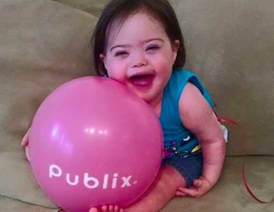 baby girl with Down syndrome holding publix balloon