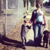 woman wearing baby carrier and walking with boy and dog on street