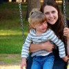 mom and young daughter sitting on playground swing