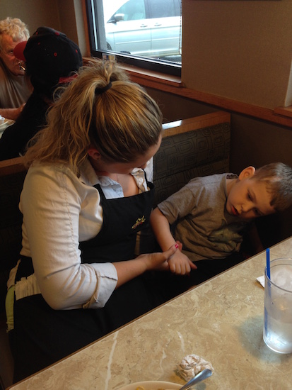 A waitress holding hands with a boy who has cerebral palsy.