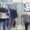 People Walking Through Entrance Door in Modern Building