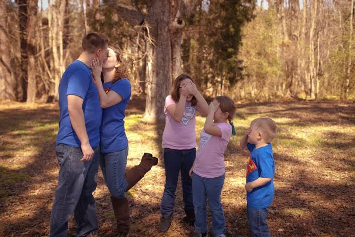 Sarah Neal and her family outside. She and her husband kiss, and her kids have their hands over their eyes.