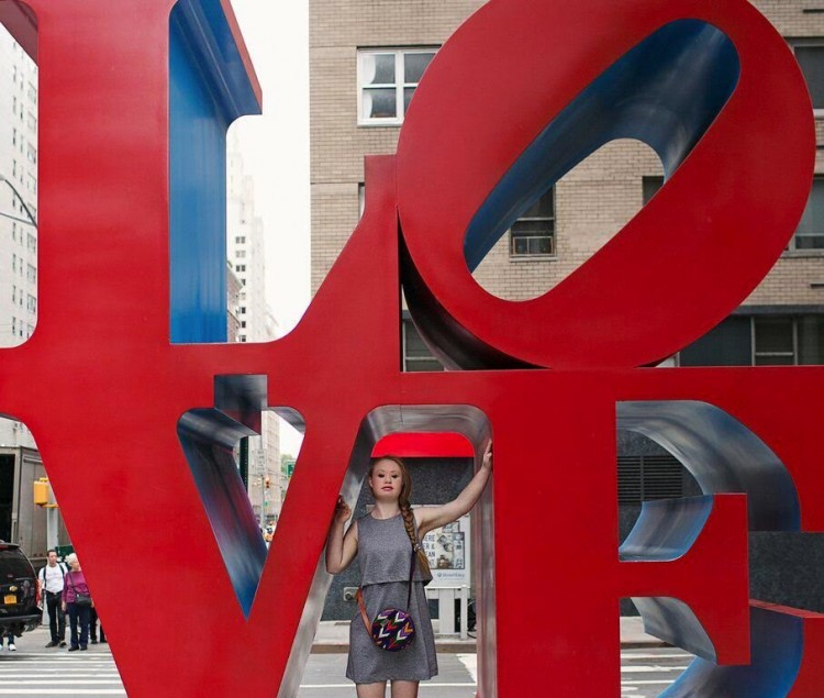 Madeline Stuart posing in between the V and E in a large red LOVE sign