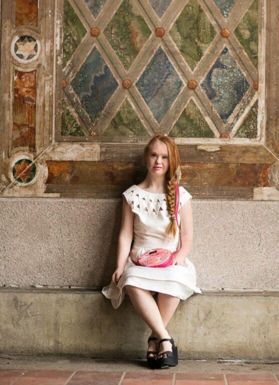 Madeline Stuart sitting in front of a building