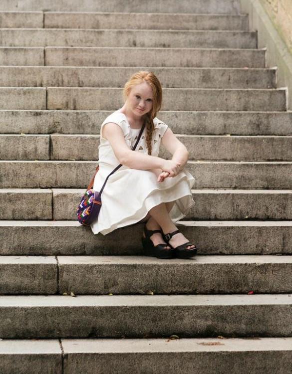 Madeline Stuart sitting on steps