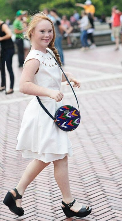Madeline Stuart walking with a colorful purse