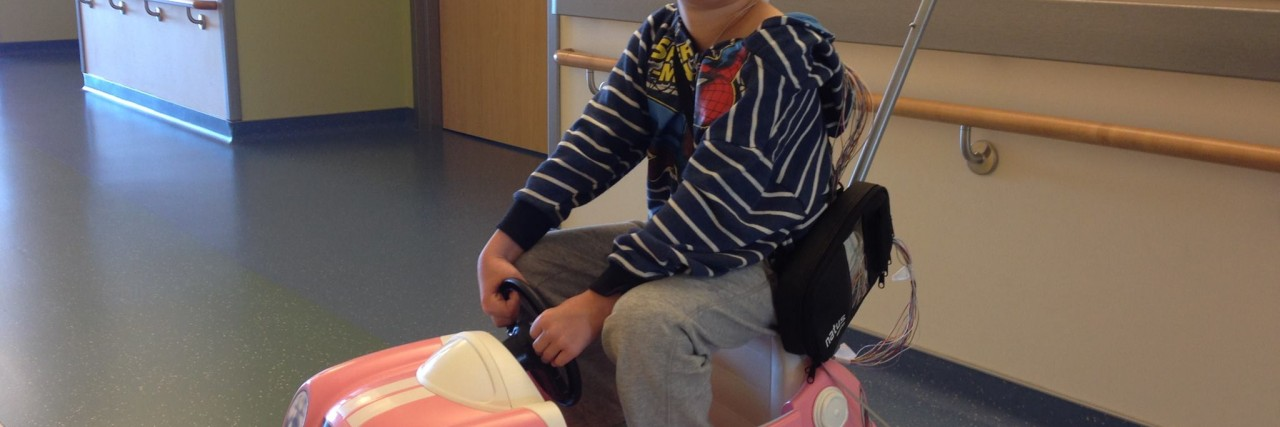 Boy with bandage around his head rides in pink toy car in hospital