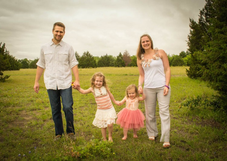 family posing for a photo in a field
