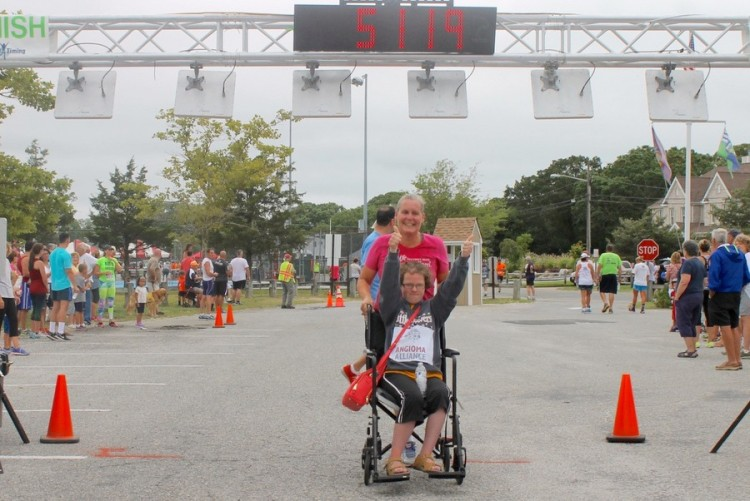 Eileen Benthal, pushing her daughter Johanna in a wheelchair crosses the finish line in the Jamesport Fire Department Sound-to-Bay footrace on August 23. (Photo credit: Denise Civiletti/RiverheadLOCAL.com)
