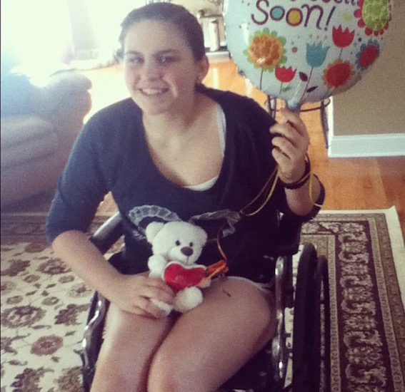 young woman with 'get well soon' balloon and teddy bear