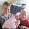 three boys holding their baby sister in the NICU
