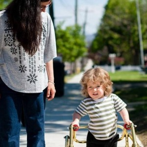 boy with walker walking down street with mom