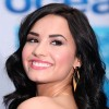 A picture of Demi Lovato, a dark-haired young woman, smiling as she looks over her shoulder