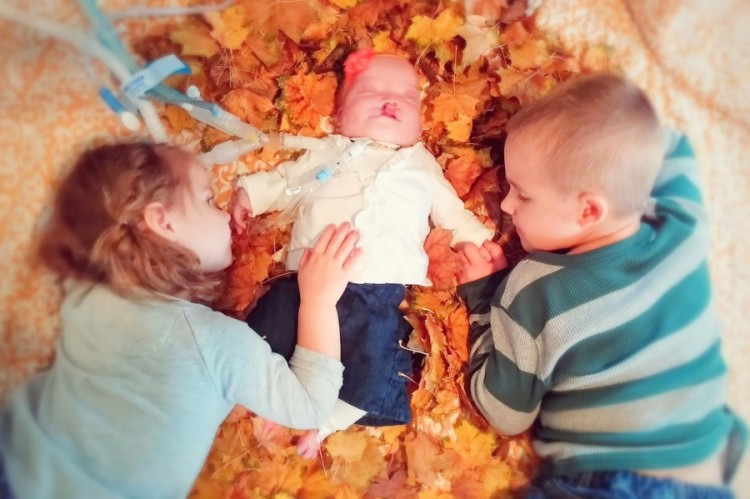 baby laying in fall leaves between two older siblings