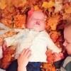 baby laying in fall leaves between two older siblings