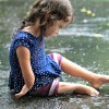 A small toddler sits in the rain looking at an object under her foot