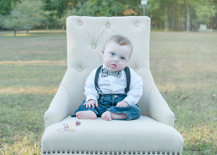 Baby wearing bow tie and suspenders sitting on a chair in a park