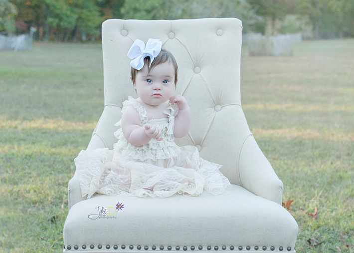 Baby with a bow sitting in chair in a park