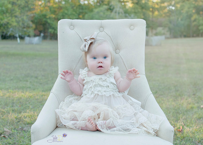 Baby girl sitting on a chair in a park